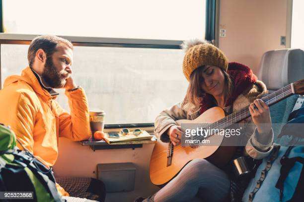 couple traveling in train and playing the guitar - martin guitar stock photos and pictures