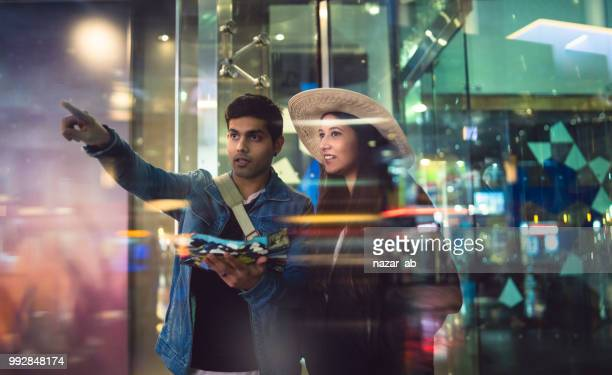 Couple traveling through city and checking map.