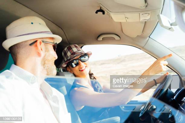 couple travelling in a van pointing to their next destination. - former stock pictures, royalty-free photos & images