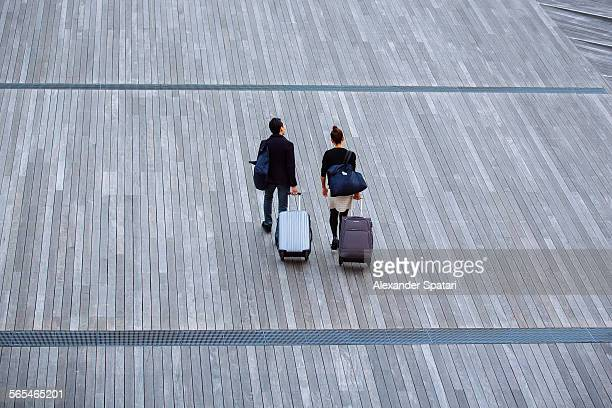 Couple travelling with luggage on wheels