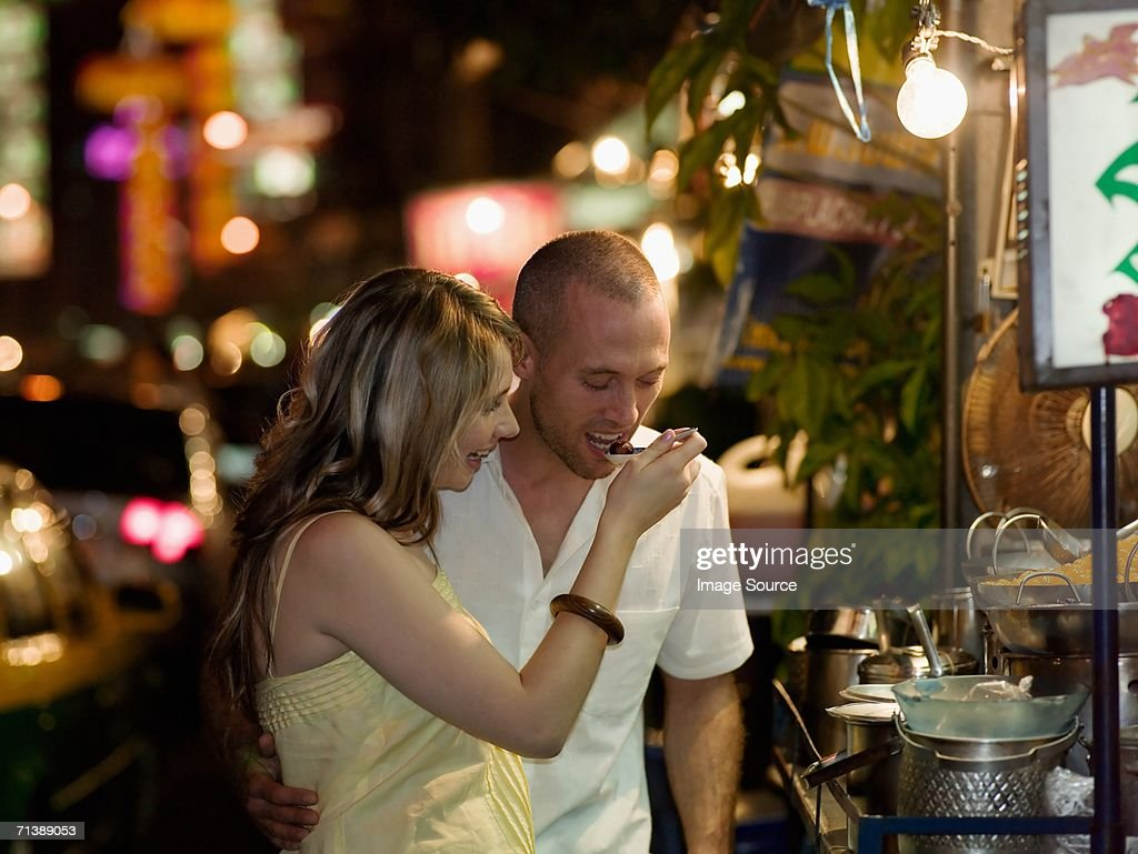Couple trying food from street vendor : Stock Photo