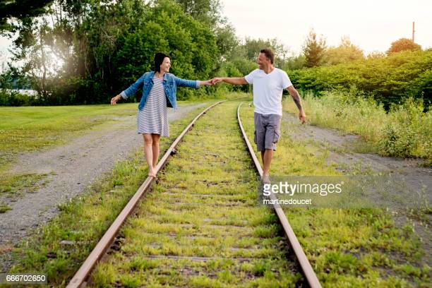 Couple trying to balance their way on railroad track.