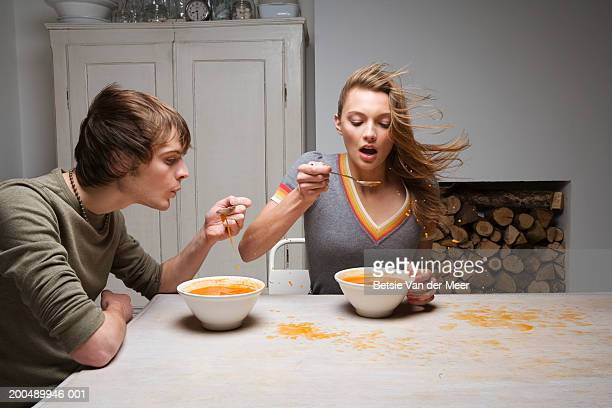 Couple trying to eat soup as strong gust of wind blows through kitchen