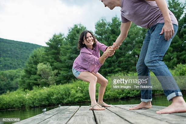 a couple trying to pull each other into the water off a jetty - rough housing stock photos and pictures