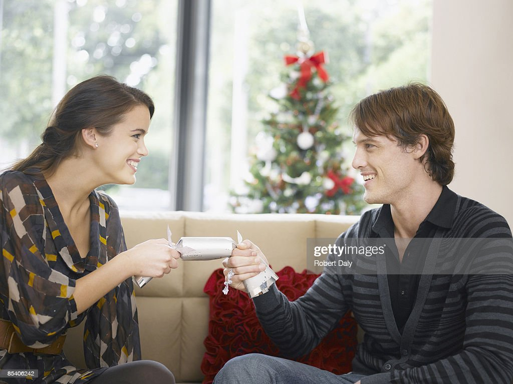 Couple tugging on Christmas cracker : Stock Photo