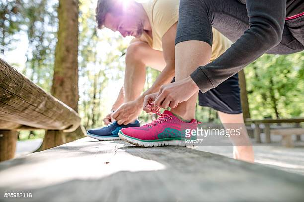 Couple tying shoes