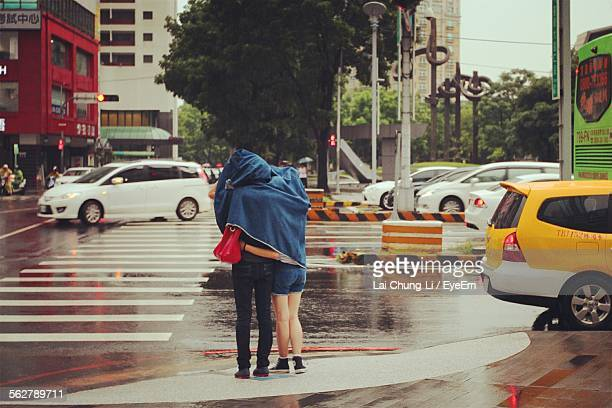 Couple Under Jacket Standing On City Street During Rainy Season