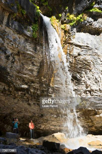 couple under spouting rock waterfall at hanging lake trail, colorado - beaver creek colorado stock pictures, royalty-free photos & images