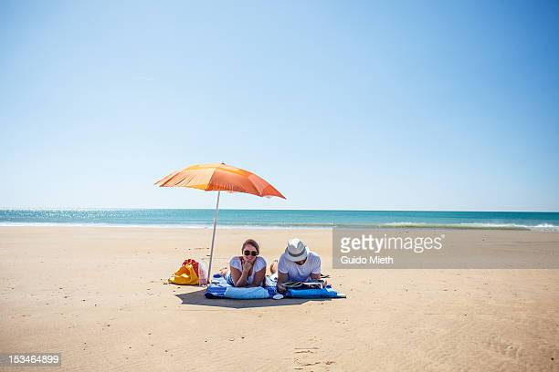 couple under sunshade - sombrilla de playa fotografías e imágenes de stock