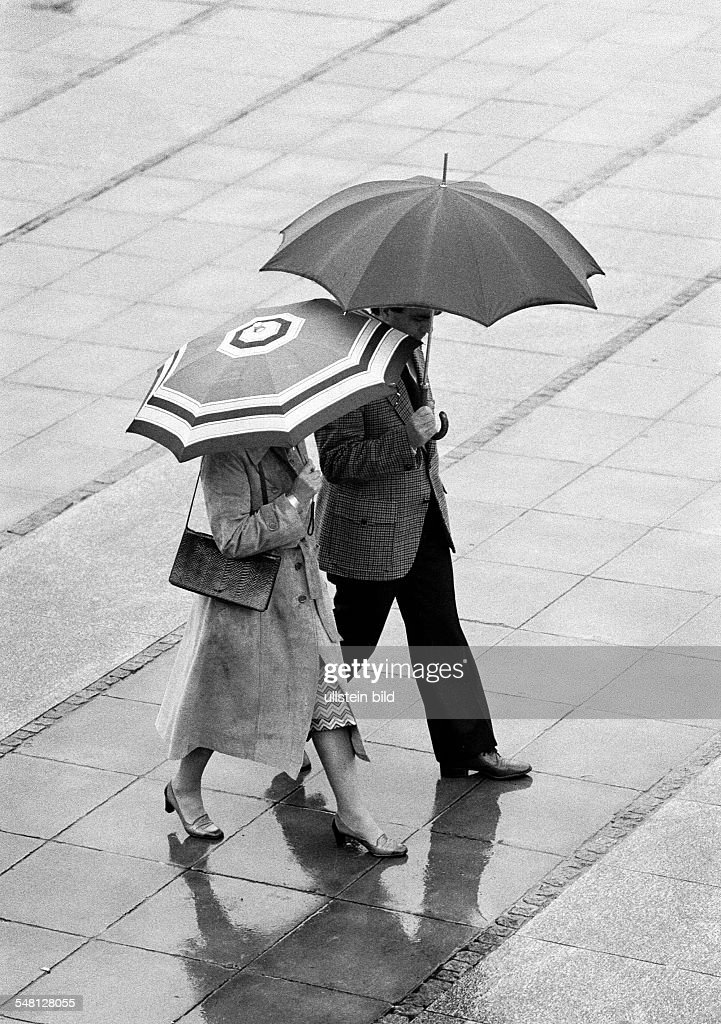 couple undertakes a walk in the rain, umbrellas, aged 30 to 40 years - 15.07.1980 : News Photo