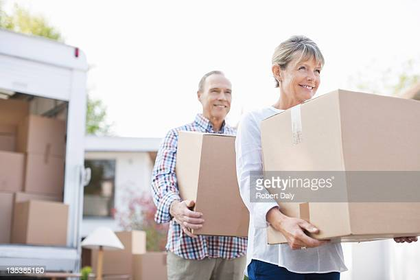 couple unloading boxes from moving van - heteroseksueel koppel stockfoto's en -beelden