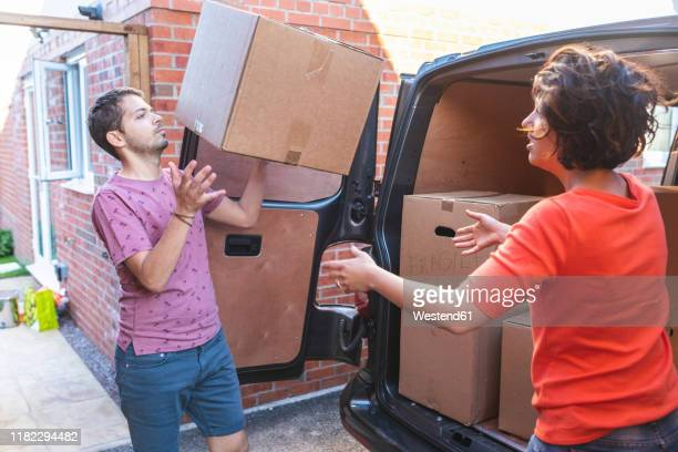 couple unloading cardboard boxes from van - flick stock pictures, royalty-free photos & images