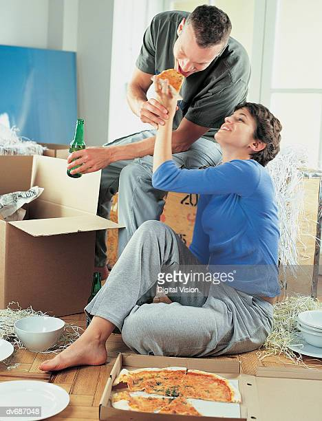 Couple Unpacking Boxes and Eating Pizza