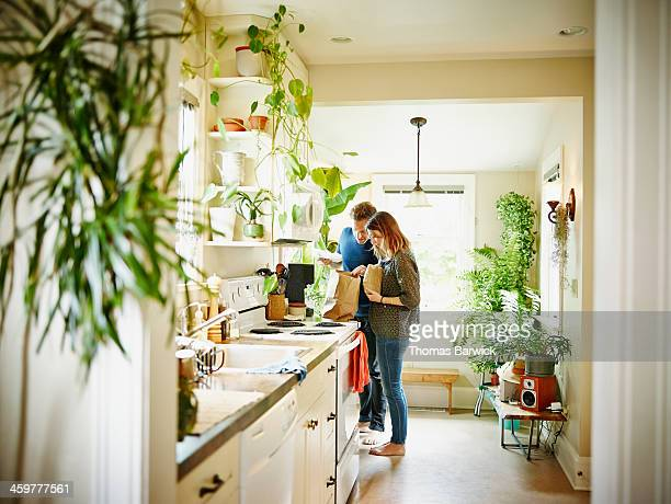 couple unpacking groceries in kitchen of home - unpacking stock pictures, royalty-free photos & images