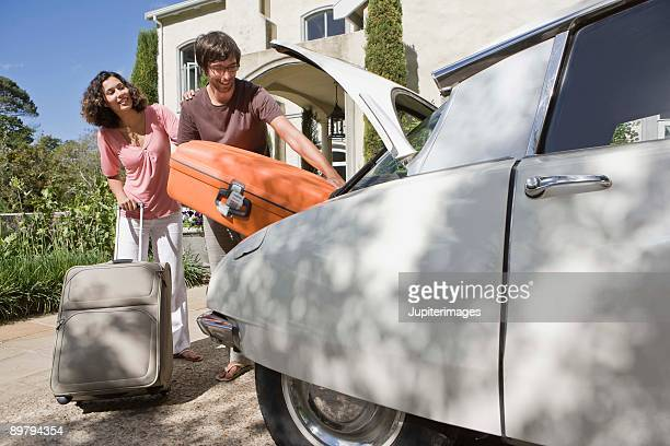Couple unpacking luggage from car trunk by hotel