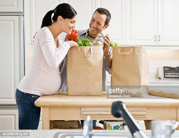 Couple unpacking shopping bag in kitchen
