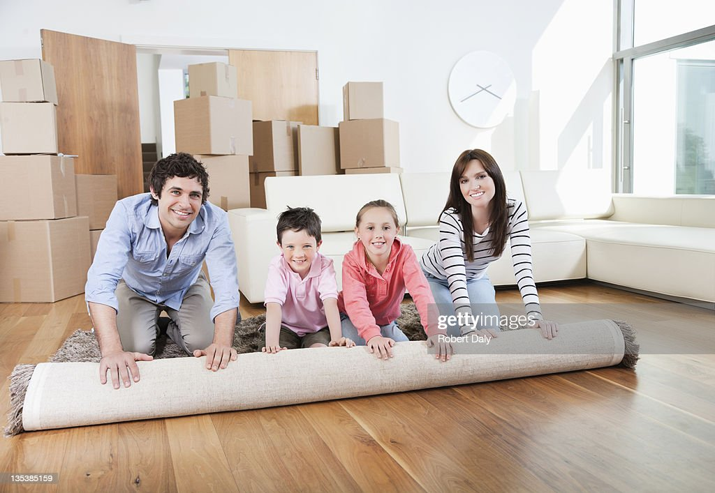 Couple unrolling carpet in new home : Stock Photo