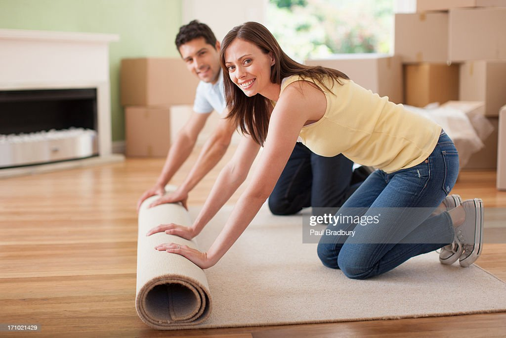 Couple unrolling carpet in new house : Stock Photo