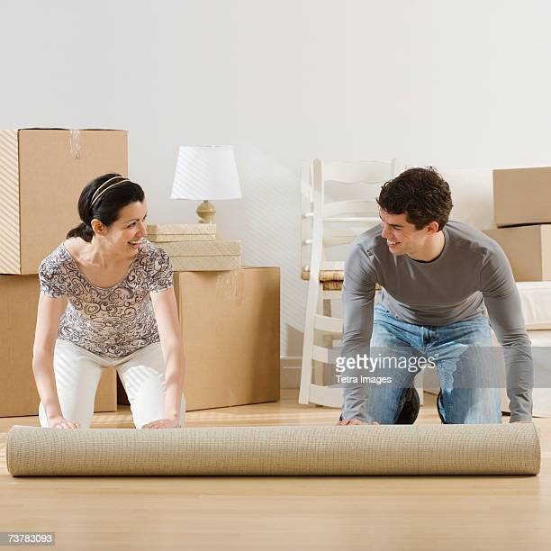 Couple unrolling rug in new house