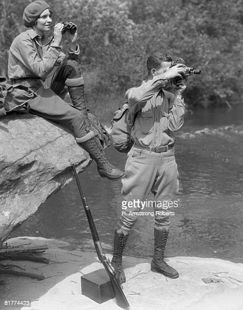 Couple upland hunt near streamside, with field glasses and gun.