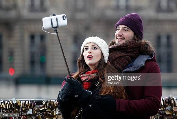 A couple use a selfiestick to take a picture of themselves in front of the love padlocks on the Pont Neuf during Valentine's Day on February 14 2016...