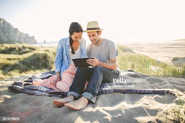 Couple use digital tablet in sand dunes, beach