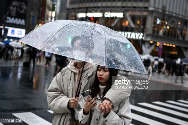 Couple uses an umbrella to shelter from the rain while crossing a street in Tokyo on October 19, 2020.