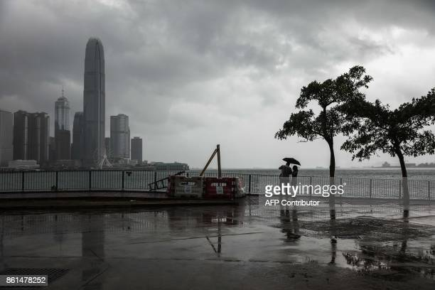 A couple uses an umbrella to shield themselves from the rain in Hong Kong on October 15 2017 as Typhoon Khanun moves across the northern part of the...