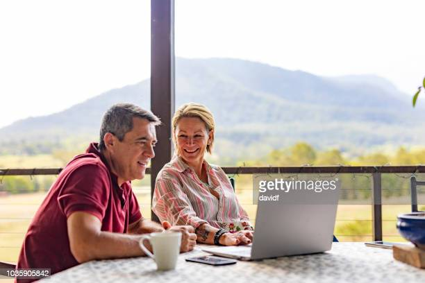 couple using a computer at their farm - scena rurale foto e immagini stock