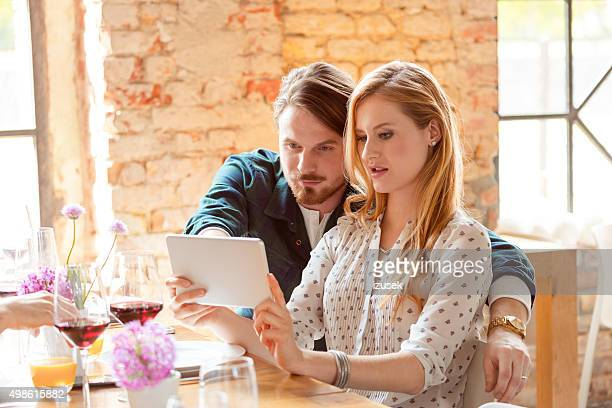 Couple using a digital tablet during lunch in the restaurant
