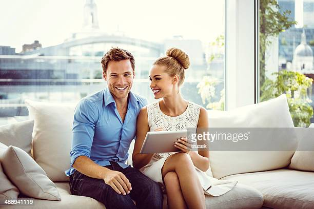 couple using a digital tablet - women of penthouse stock photos and pictures