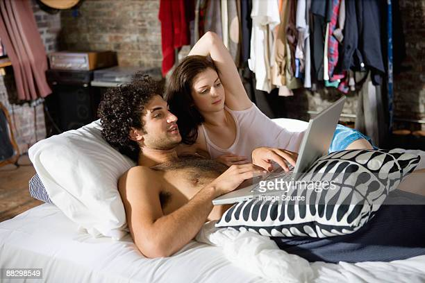 Couple using a laptop computer in bed