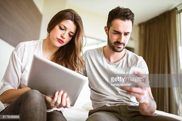 Casal usando um telefone móvel sentado na cama