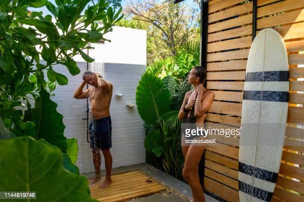 couple using an outdoor shower after surfing - casal chuveiro imagens e fotografias de stock