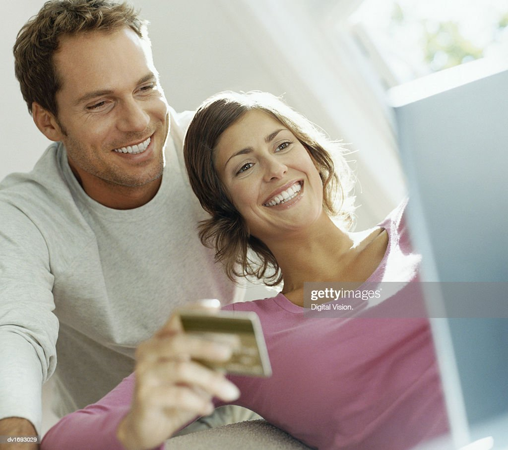 Couple Using Bank Card Online With a Laptop : Stock Photo