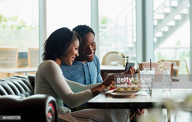 Couple using cell phone at lunch in cafe