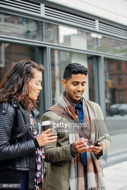 Couple using cell phone in city