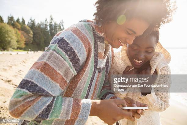 Couple using cell phone on beach