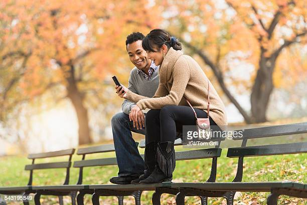 Couple using cell phone on park bench