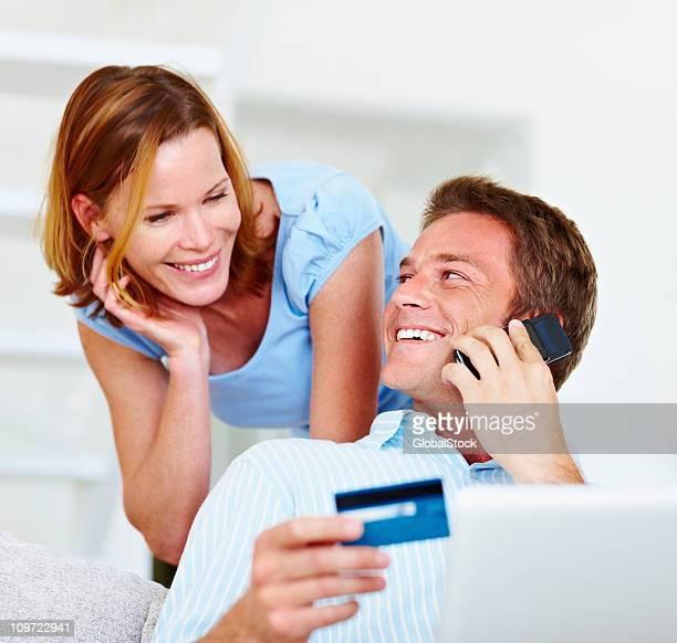 Couple à l'aide de téléphone portable et de carte de crédit pour effectuer des réservations en ligne