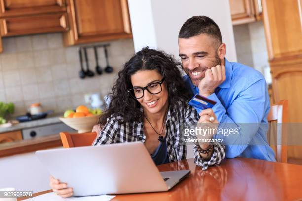 Couple using credit card at home