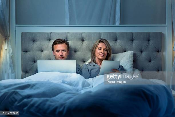 Couple using digital tablet and laptop on bed
