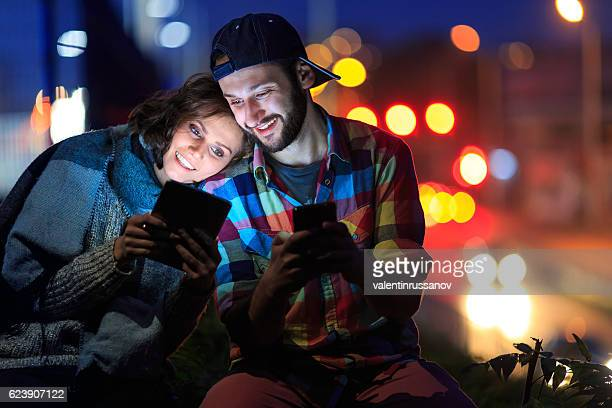 Couple using digital tablet and smart phone at night