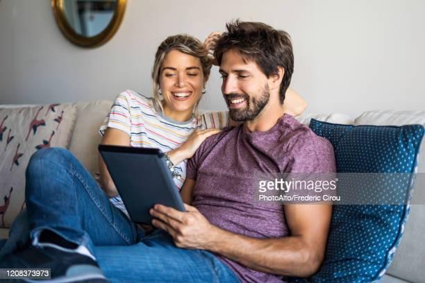 couple using digital tablet at home - tablette photos et images de collection
