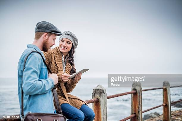 Couple using digital tablet at seaside railing