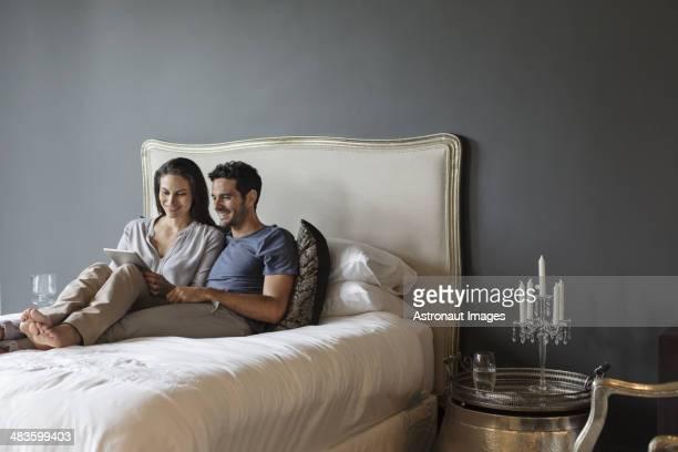 Couple à l'aide de tablette numérique dans la chambre