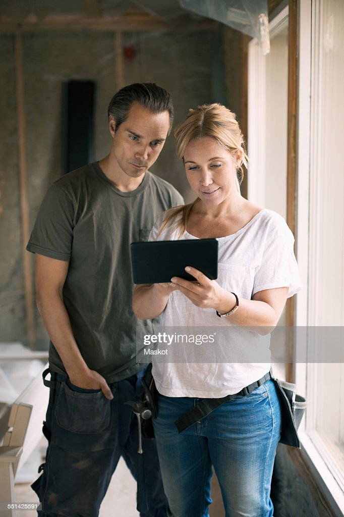 Couple using digital tablet in house being renovated : Stock Photo