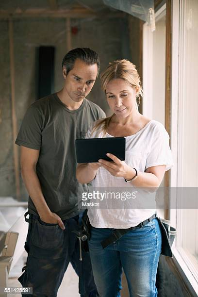 Couple using digital tablet in house being renovated