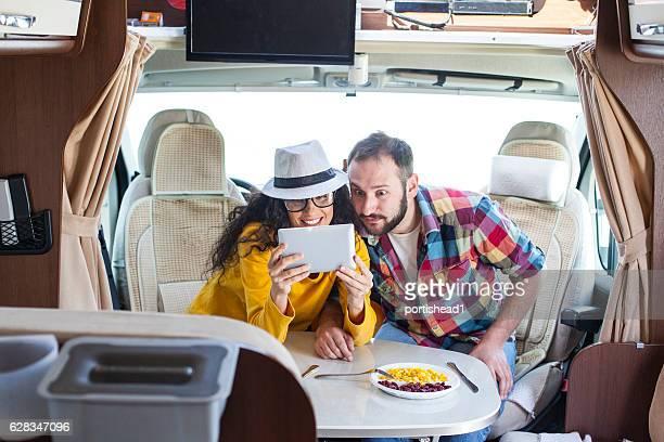 Couple using digital tablet inside of caravan