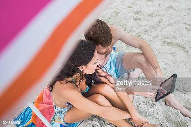 Couple using digital tablet on beach